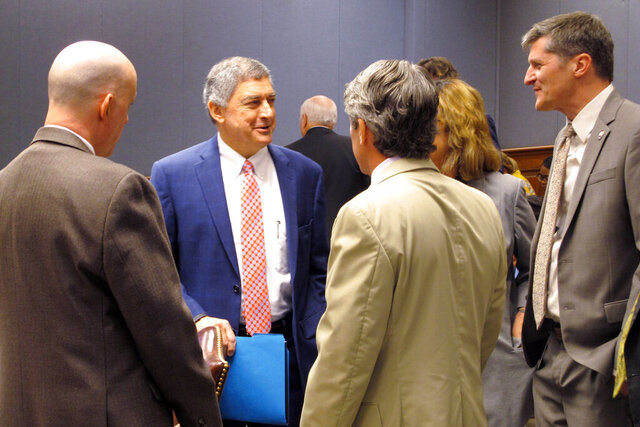 File-This Sept. 13, 2019, file photo shows Commissioner of Administration Jay Dardenne, second from left, the governor's chief budget adviser, speaking to budget analysts and lawmakers at the House and Senate budget committee meeting, in Baton Rouge, La. Gov. John Bel Edwards' administration accused Louisiana's treasurer and other state leaders Thursday of sidelining one of the nation's largest banks from working on multimillion-dollar state borrowing deals because of the bank's firearm restriction policies for corporate customers. (AP Photo/Melinda Deslatte, File)