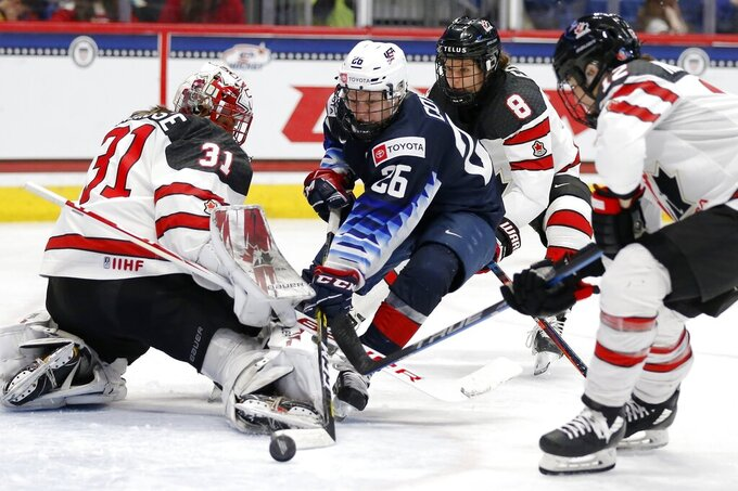 FILE - In this Saturday, Dec. 14, 2019 file photo, Canada's Geneviève Lacasse (31) blocks a shot by United States' Kendall Coyne Schofield (26) during the third period of a rivalry series women's hockey game in Hartford, Conn. The puck drops on a women's world hockey championship more than two years after the last one on Friday Aug. 20, 2021. Who's counting? American forward Kendall Coyne Schofield is, for one..(AP Photo/Michael Dwyer, File)