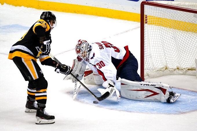 Pittsburgh Penguins' Jake Guentzel, left, puts a shot under the glove hand of Washington Capitals goaltender Ilya Samsonov (30) for a goal during a shootout in an NHL hockey game in Pittsburgh, Sunday, Jan. 17, 2021. (AP Photo/Gene J. Puskar)
