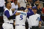 Arizona Diamondbacks' Eduardo Escobar (5) is congratulated by Ketel Marte, left, and manager Torey Lovullo, right, after scoring against the Los Angeles Dodgers during the fourth inning of a baseball game Thursday, Aug. 29, 2019, in Phoenix. (AP Photo/Ross D. Franklin)