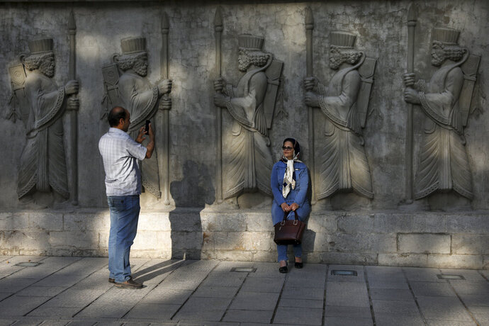 In this Saturday, May 18, 2019 photo, a couple takes photos with bas reliefs of ancient Persian soldiers in an old neighborhood in downtown Tehran, Iran. The Associated Press spoke to a variety of people on Tehran's streets recently, ranging from young and old, women wearing the all-encompassing black chador to those merely loosely covering their hair. (AP Photo/Vahid Salemi)