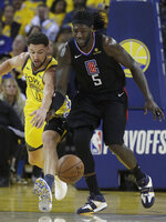 Golden State Warriors guard Klay Thompson, left, and Los Angeles Clippers forward Montrezl Harrell (5) go after a loose ball during the first half of Game 2 of a first-round NBA basketball playoff series in Oakland, Calif., Monday, April 15, 2019. (AP Photo/Jeff Chiu)