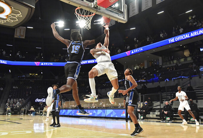 Georgia Tech guard Jordan Usher (4) shoots next to Duke center Mark Williams (15) during the first half of an NCAA college basketball game Tuesday, March 2, 2021, in Atlanta. (Hyosub Shin/Atlanta Journal-Constitution via AP)