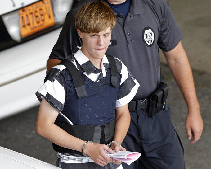FILE - In this June 18, 2015 file photo, Charleston, S.C., shooting suspect Dylann Storm Roof is escorted from the Cleveland County Courthouse in Shelby, N.C. Attorneys for the federal government have opposed Roof's request for a new appellate hearing, arguing that the South Carolina man was properly convicted and sentenced for the 2015 racist slayings of nine members of a Black congregation. (AP Photo/Chuck Burton, File)