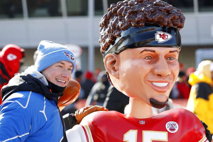 A Tennessee Titans fan has a picture taken outside Arrowhead Stadium with a bobble head of Patrick Mahomes, before the NFL AFC Championship football game against the Kansas City Chiefs Sunday, Jan. 19, 2020, in Kansas City, MO. (AP Photo/Charlie Neibergall)