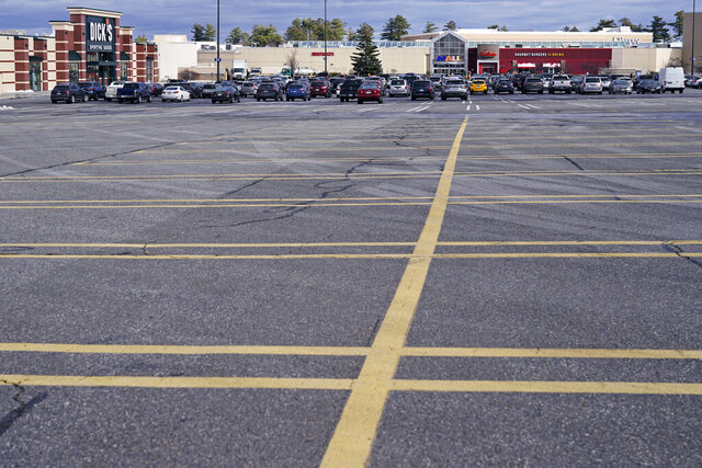 A parking lot nearly empty of the cars of holiday shoppers is shown at the Mall of New Hampshire, Thursday, Dec. 10, 2020, in Manchester, N.H. Retail sales fell 1.1% in November, the biggest drop in seven months, a sign that Americans held back on spending during the start of the holiday shopping season. The U.S. Commerce Department also revised October's number, saying on Wednesday that retail sales actually fell 0.1% that month, instead of rising 0.3% as it previously reported. (AP Photo/Charles Krupa)