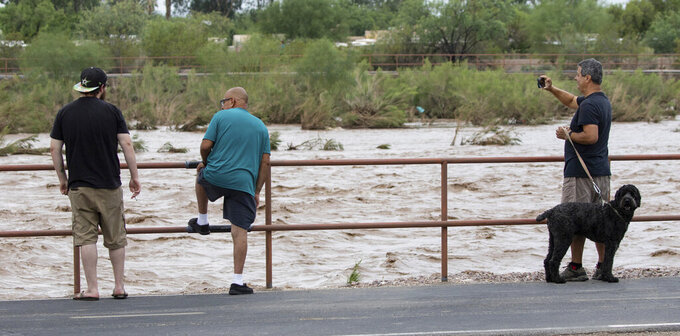 The Rillito River rolling along just west of Swan Road after a powerful storm with heavy rain landed over the Tucson area, Ariz., early Friday, July 23, 2021. (Rick Wiley/Arizona Daily Star via AP)