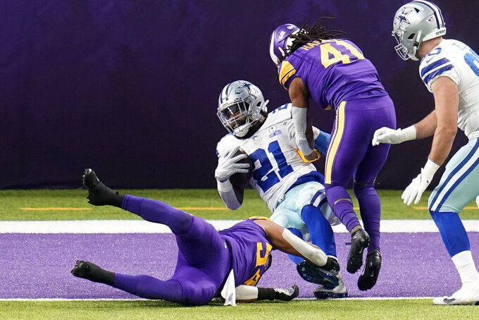 Dallas Cowboys running back Ezekiel Elliott (21) scores on a 6-yard touchdown reception over Minnesota Vikings linebacker Eric Kendricks (54) during the first half of an NFL football game, Sunday, Nov. 22, 2020, in Minneapolis. (AP Photo/Jim Mone)