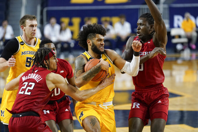 Michigan Wolverines forward Isaiah Livers (2) drives between Rutgers guard Caleb McConnell (22) and Rutgers center Cliff Omoruyi (5) in the first half of an NCAA college basketball game in Ann Arbor, Mich., Thursday, Feb. 18, 2021. (AP Photo/Paul Sancya)