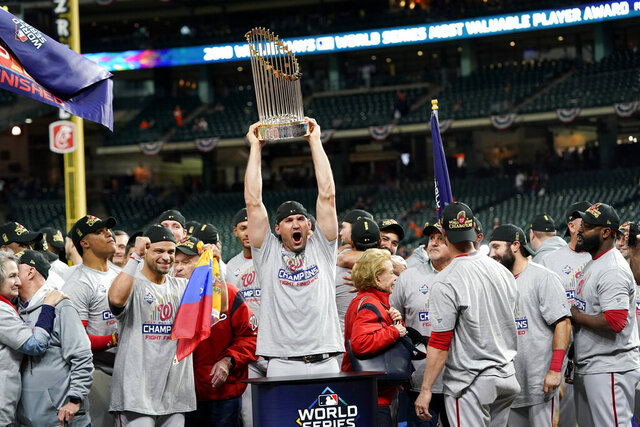 FILE - In this Oct. 30, 2019, file photo, Washington Nationals first baseman Ryan Zimmerman celebrates with the trophy after Game 7 of the baseball World Series against the Houston Astros in Houston. In the third installment of Washington Nationals star Ryan Zimmerman's diary for the AP, he discusses a fundraising initiative that has drawn support from teammates and athletes from other sports in the D.C. area to help hospital workers dealing with the coronavirus pandemic. Zimmerman also discusses what it was like to re-watch Game 7 of the World Series this week. (AP Photo/David J. Phillip, File)