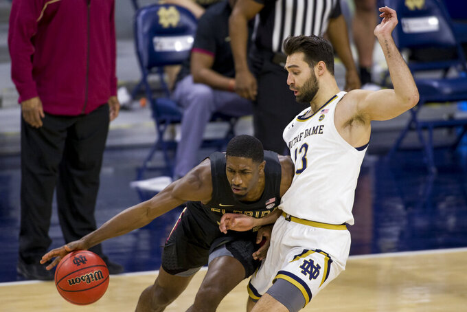 Florida State's Sardaar Calhoun, left, drives in as Notre Dame's Nikola Djogo (13) defends during the second half of an NCAA college basketball game Saturday, March 6, 2021, in South Bend, Ind. Notre Dame won 83-73. (AP Photo/Robert Franklin)