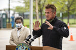 Chicago Mayor Lori Lightfoot looks on as actor and activist Sean Penn speaks during a press conference to announce a new coronavirus drive-thru testing site at Dr. Jorge Prieto Math and Science Academy, in Chicago, organized by the CORE disaster relief organization started by Penn, Monday, May 18, 2020. (Ashlee Rezin Garcia/Chicago Sun-Times via AP)