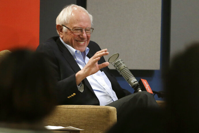 Democratic presidential candidate Sen. Bernie Sanders, I-Vt., smiles and waves while seated in front of an audience before the start of a forum broadcast on radio in a New Hampshire Public Radio station, Sunday, Jan. 19, 2020, in Concord, N.H. (AP Photo/Steven Senne)