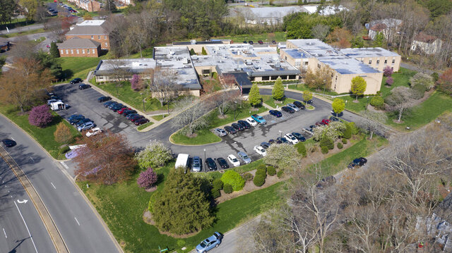 This Friday, March 27, 2020 photo shows the Canterbury Rehabilitation & Healthcare Center in Richmond, Va.  The Center is dealing with an outbreak of COVID-19 cases. Officials said Thursday that a few residents have died and dozens are showing symptoms. (AP Photo/Steve Helber)
