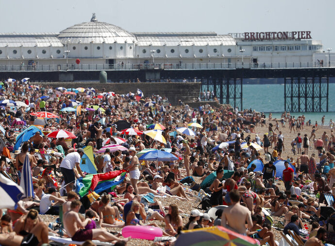 Beachgoers enjoy the sunshine and sea on what is now Britain's hottest day of the year so far, in Brighton, England, Friday, July 31, 2020. Temperatures have reached 35C (95F) at London's Heathrow Airport. (AP Photo/Alastair Grant)
