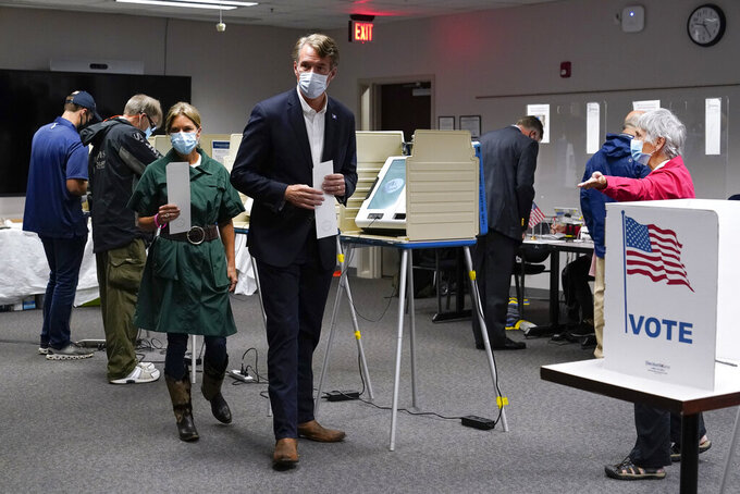 Virginia Republican gubernatorial candidate Glenn Youngkin, center, and his wife Suzanne vote early, Thursday, Sept. 23, 2021, in Fairfax, Va. (AP Photo/Patrick Semansky)