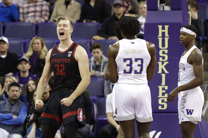 Stanford's Lukas Kisunas (32) reacts after scoring as Washington's Isaiah Stewart (33) and Nahziah Carter watch during the first half of an NCAA college basketball game Thursday, Feb. 20, 2020, in Seattle. (AP Photo/Elaine Thompson)