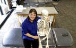 """In this Saturday, May 12, 2018, photo, April Oury, owner of Body Gears physical therapy center poses for a portrait with her instructional skeleton in Chicago. Oury started her physical therapy practice 14 years ago wanting to give all aspects of her business the same focus and attention to detail she gave patients, even when it came to choosing paint colors or an internet provider. She wouldn't do it that way again. """"There was not enough time in the day or the workweek to put that kind of effort into every single thing,"""" says Oury. (AP Photo/Charles Rex Arbogast)"""