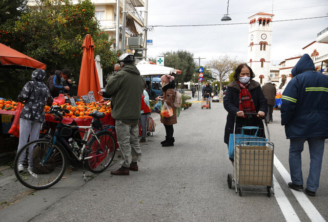 People wearing face masks to prevent the spread of coronavirus, shop at an open-air fruit and vegetable market in Athens, Friday, Jan. 15, 2021. Greece's prime minister says the country's retail sector might begin to gradually reopen next week, if the scientists advising the government on the coronavirus pandemic recommend it is safe to do so. (AP Photo/Thanassis Stavrakis)