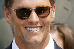 The Vince Lombardi Trophy is reflected in Tampa Bay Buccaneers quarterback Tom Brady's glasses as attends a ceremony on the South Lawn of the White House, in Washington, Tuesday, July 20, 2021, where President Joe Biden honored the Super Bowl Champion Tampa Bay Buccaneers for their Super Bowl LV victory. (AP Photo/Andrew Harnik)