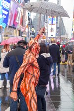 This photo provided by Andy Golub shows a nude model taking part in the Polar Bear Paint body-painting event in New York City's Times Square frolics with his umbrella during the rain and cold on Saturday Feb. 10, 2018. (Andy Golub via AP)