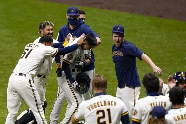 Players congratulate Milwaukee Brewers' Keston Hiura after his walk off sacrifice fly during the eighth inning of the first game of a baseball doubleheader against the St. Louis Cardinals Monday, Sept. 14, 2020, in Milwaukee. The Brewers won 2-1. (AP Photo/Morry Gash)