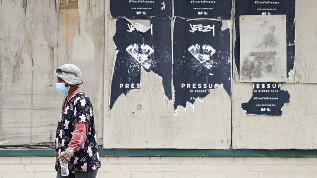 A woman walks past a boarded up business, Thursday, May 28, 2020, in East Cleveland, Ohio. The state says about 1.3 million Ohioans have filed unemployment claims in the past 10 weeks as Ohio's stay-at-home order depressed the economy and led to widespread layoffs. The Ohio Department of Job and Family Services says about 42,000 people filed claims for the week ending May 23. (AP Photo/Tony Dejak)