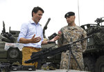 Canadian Prime Minister Justin Trudeau, left, speaks to a Latvian soldier as he inspects the troops as he visits Adazi Military Base in Kadaga, Latvia, on Tuesday, July 10, 2018. Canadian prime minister says he hopes the upcoming NATO summit will send a message of broad support for unity and solidarity but acknowledges that there will