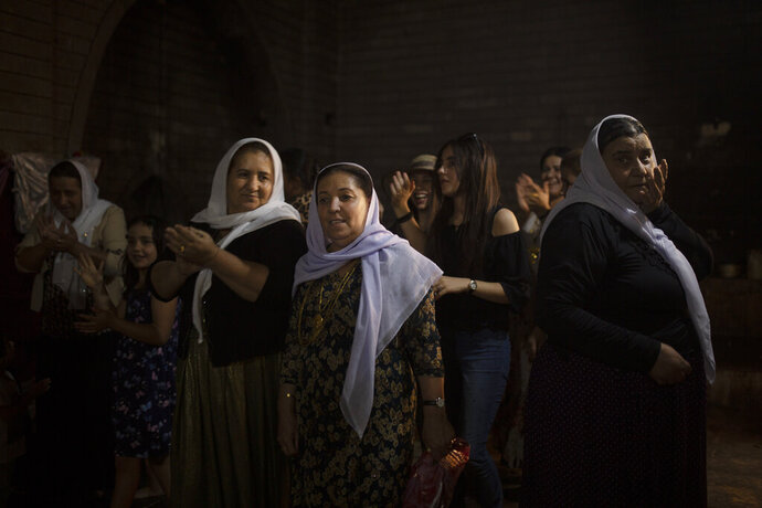 In this Sept. 12, 2019 photo, Yazidi women visit Lalish, the holiest Yazidi shrine, in Iraq's Dohuk province, in northern Iraq. During a week-long assault by Islamic State militants in 2014, they killed hundreds of Yazidis and abducted 6,417, more than half of them women and girls. (AP Photo/Maya Alleruzzo)