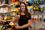 Charm City Puppies manager Becky Schmidt poses with a puppy at a pet store in Columbia, Md., Monday, Aug. 26, 2019. Pet stores are suing to block a Maryland law that will bar them from selling commercially bred dogs and cats, a measure billed as a check against unlicensed and substandard