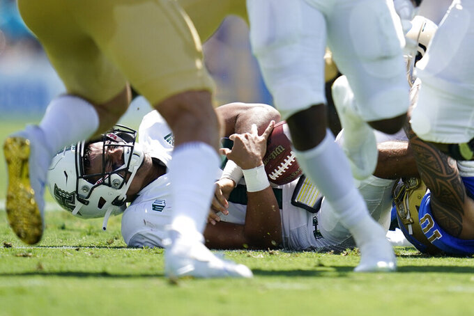 Hawaii Warriors quarterback Chevan Cordeiro (12) is sacked by UCLA Bruins linebacker Ale Kaho (10) during the first half of an NCAA college football game Saturday, Aug. 28, 2021, in Pasadena, Calif. (AP Photo/Ashley Landis)