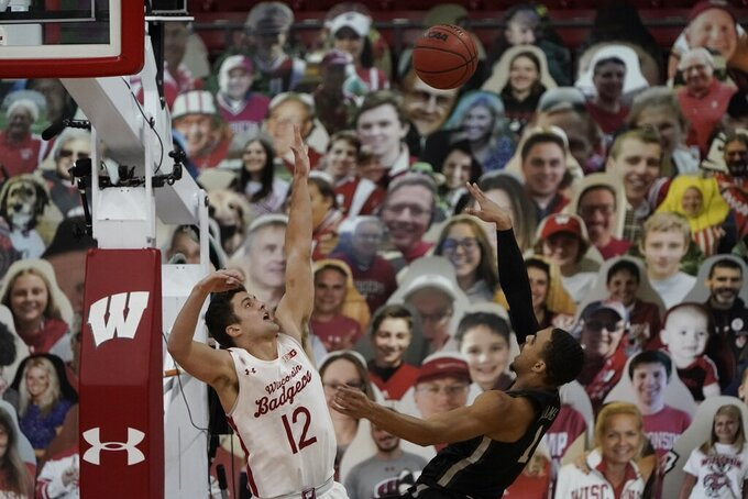 Minnesota's Tre' Williams shoots over Wisconsin's Trevor Anderson (12) during the first half of an NCAA college basketball game Thursday, Dec. 31, 2020, in Madison, Wis. (AP Photo/Morry Gash)