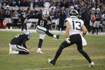 Oakland Raiders kicker Daniel Carlson misses the first of two field goal attempts late in the second half of an NFL football game against the Jacksonville Jaguars in Oakland, Calif., Sunday, Dec. 15, 2019. Jacksonville won the game 20-16. Holding the ball was the Raiders' A.J. Cole and at right is Jacksonville Jaguars wide receiver Michael Walker (13). (AP Photo/Ben Margot)