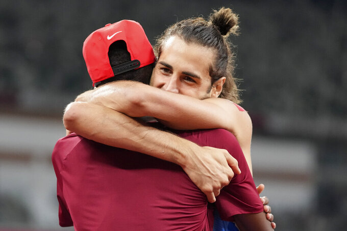 FILE - In this Aug. 1, 2021, file photo, Gianmarco Tamberi, of Italy, embraces fellow gold medalist Mutaz Barshim, of Qatar, after the final of the men's high jump at the 2020 Summer Olympics in Tokyo. In an extraordinary Olympic Games where mental health has been front and center, acts of kindness are everywhere. The world's most competitive athletes have been captured showing gentleness and warmth to one another — celebrating, pep-talking, wiping away each another's tears of disappointment.  (AP Photo/Matthias Schrader, File)