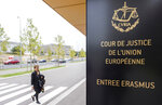 FILE - In this file photo taken on Monday, Oct. 5, 2015 a woman walks by the entrance to the European Court of Justice in Luxembourg. The European Union moved Tuesday to force Poland to comply with the rulings of Europe's top court with plans to seek daily fines against the nationalist government in Warsaw linked to a long-running dispute over justice independence in the country. (Geert Vanden Wijngaert, File)