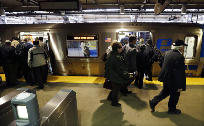 FILE- In this April 4, 2014 file photo, commuters board a PATH train in Newark, N.J. In a plan announced Thursday, June 20, 2019 by the Port Authority of New York and New Jersey, PATH trains connecting northern New Jersey with New York City are going to be longer and more frequent in coming years as a means to address overcrowding that figures to become more acute as thousands of residential units and parking spaces spring up around train stations. (AP Photo/Mel Evans, File)