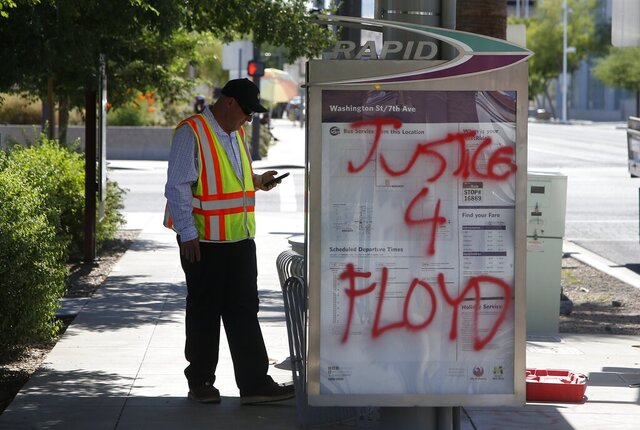 A City of Phoenix worker stands near graffiti at a bus stop, Friday, May 29, in Phoenix, in the aftermath of a demonstration protesting the death of George Floyd, a handcuffed black man who died in police custody Monday with much of the arrest captured on video of a Minneapolis police officer kneeling on the neck of Floyd. (AP Photo/Ross D. Franklin)
