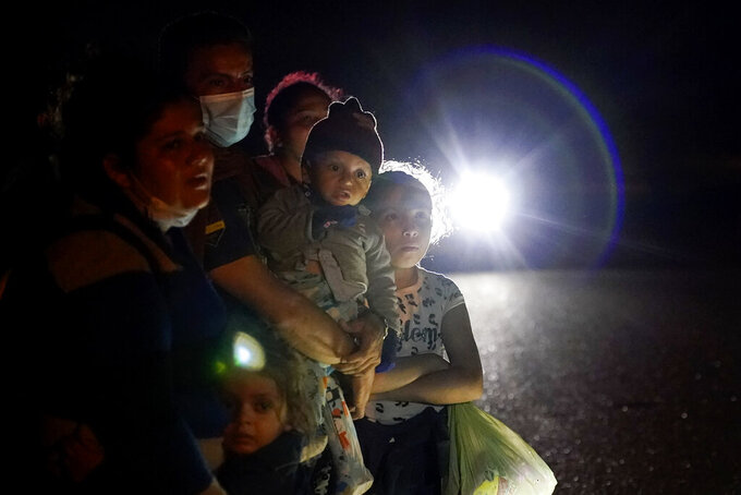 FILE - In this May 17, 2021 file photo, a group of migrants mainly from Honduras and Nicaragua wait along a road after turning themselves in upon crossing the U.S.-Mexico border, in La Joya, Texas. The Biden administration announced Tuesday, June 15, 2021, that it was expanding a newly-revived effort to bring Central American children to the United States to reunite with parents legally living in the country. (AP Photo/Gregory Bull, File)