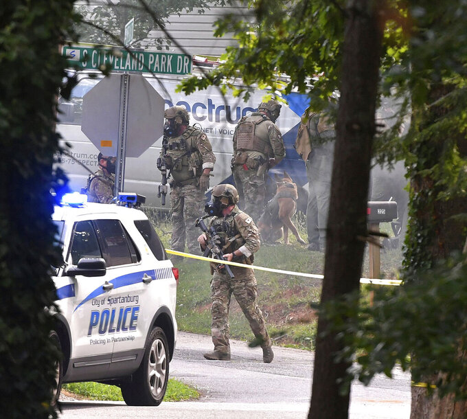 Officers and investigators with the Spartanburg Police Department, Spartanburg County Sheriff's Office, and South Carolina Law Enforcement Division gather at the scene of a fatal shooting and standoff in Spartanburg, S.C., Thursday, July 1, 2021. (Tim Kimzey/Spartanburg Herald-Journal via AP)