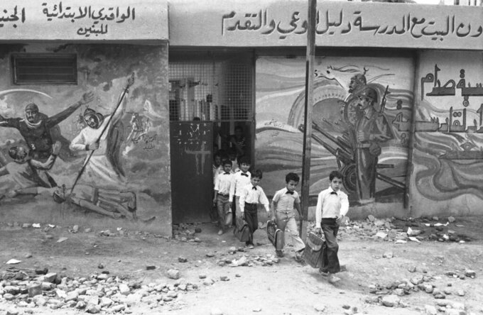 FILE - In this April 28, 1984 file photo, elementary school pupils, dressed in the standard white shirt school uniform of Iraq, leave their school in Baghdad. Scenes on the wall depict the Iraq-Iran war as a new battle between Arabia and Persia. The Iran-Iraq war launched by Iraq's Saddam Hussein after the Iranian revolution resulted in around half a million deaths. A generation was decimated in both countries. (AP Photo/Herve Merliac)
