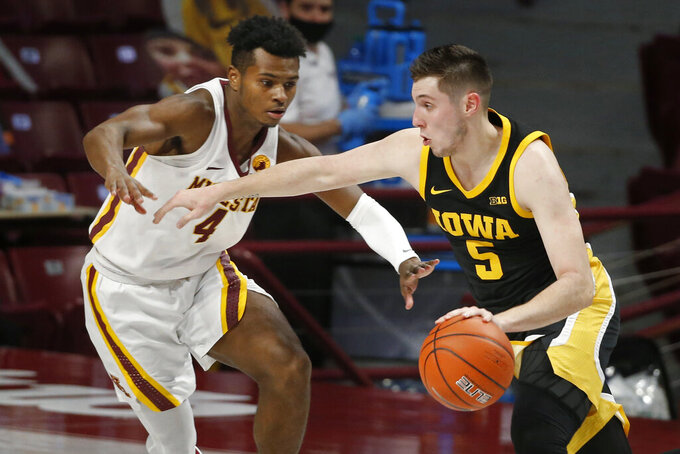 Iowa guard CJ Fredrick (5) drives around Minnesota guard Jamal Mashburn Jr. (4) during the first half of an NCAA college basketball game Friday, Dec. 25, 2020, in Minneapolis. (AP Photo/Bruce Kluckhohn)