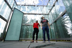 Chloe Taub and Anthony Brobenzano, of Hollywood, Fla., look at the 9/11 memorial at Logan International Airport, Thursday, Aug. 19, 2021, in Boston. The two were the only visitors during a three-hour span that afternoon. Tucked in a grove of ginkgo trees, the glass cube at Logan Airport pays tribute to those lost aboard the two jetliners that took off from Boston and were hijacked by terrorists who flew them into the World Trade Center towers. But it's mostly silent homage. The memorial etched with the names of those who perished aboard American Airlines Flight 11 and United Airlines Flight 175 draws few visitors. (AP Photo/Elise Amendola)