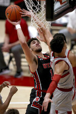 Utah forward Timmy Allen (1) scores against Stanford forward Jaiden Delaire during the first half of an NCAA college basketball game Saturday, Feb. 13, 2021, in Stanford, Calif. (AP Photo/Scot Tucker)