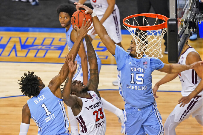 Virginia Tech guard Tyrece Radford (23) goes up for a shot as North Carolina forward Garrison Brooks (15) blocks and teammate guard Leaky Black (1) helps out during the first half of an NCAA college basketball game in the quarterfinal round of the Atlantic Coast Conference tournament in Greensboro, N.C., Thursday, March 11, 2021. (AP Photo/Gerry Broome)