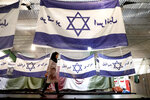 In this Saturday, Feb. 8, 2020 photo, a worker walks past Israeli flags with a slogan in Persian which reads,