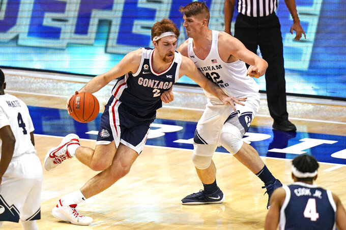 Gonzaga forward Drew Timme (2) drives as BYU center Richard Harward (42) defends in the first half of an NCAA college basketball game, Monday, Feb. 8, 2021, in Provo, Utah. (AP Photo/Rick Bowmer)