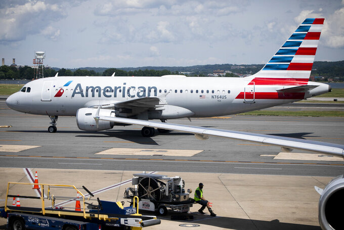 This June 2, 2021  photo shows an American Airlines aircraft at Ronald Reagan Washington National Airport in Arlington, Va.  American Airlines is cutting flights to protect its network from getting overloaded as summer travel season arrives. American scrubbed more than 130 flights by Tuesday, June 22  according to tracking service FlightAware.  (AP Photo/Jenny Kane)