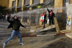 Anti-government demonstrators throw stones toward riot police during a protest against a parliament session for a vote of confidence for the new government in downtown Beirut, Lebanon, Tuesday, Feb. 11, 2020. (AP Photo/Bilal Hussein)