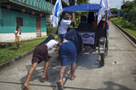 Young female members of the Israelites of the New Universal Pact religious group, push an overloaded motorbike taxi up a hill during an Agricultural People's Front of Peru or Frepap campaign rally, in San Pablo, Peru, Tuesday, March 30, 2021. Analysts say Frepap's clean image and backing in distant or impoverished communities far away from media and pollsters could produce an April 11 electoral surprise. (AP Photo/Rodrigo Abd)