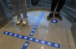 Customers stand in an elevator with the floor demarcated with social distancing stickers during a relaxation of the COVID-19 lockdown rules, at the El Recreo mall in Caracas, Venezuela, Wednesday, June 17, 2020. (AP Photo/Matias Delacroix)